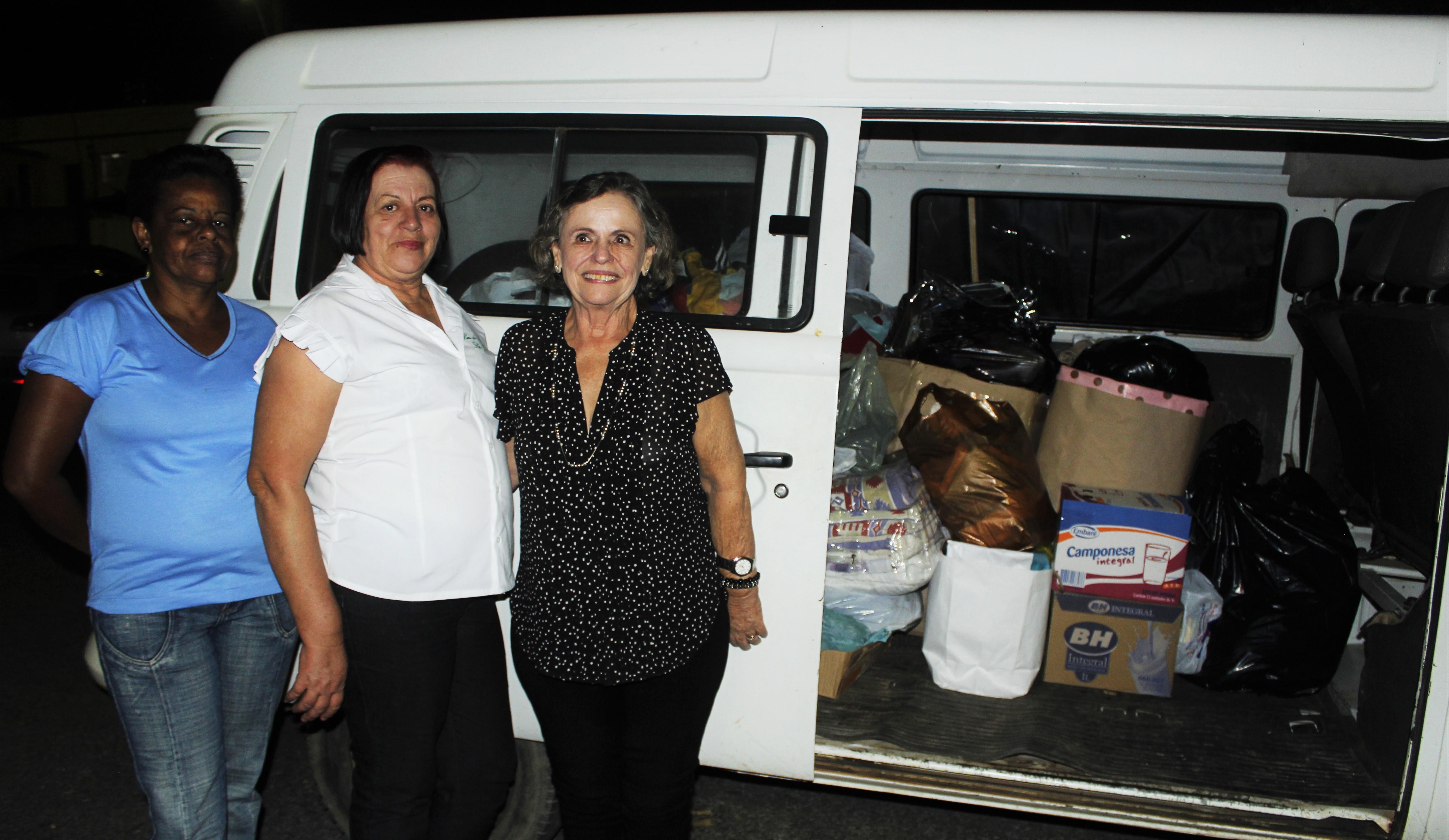 D. Ivone (a direita), as voluntárias do Asilo São José e ao fundo a Kombi cheia de doações